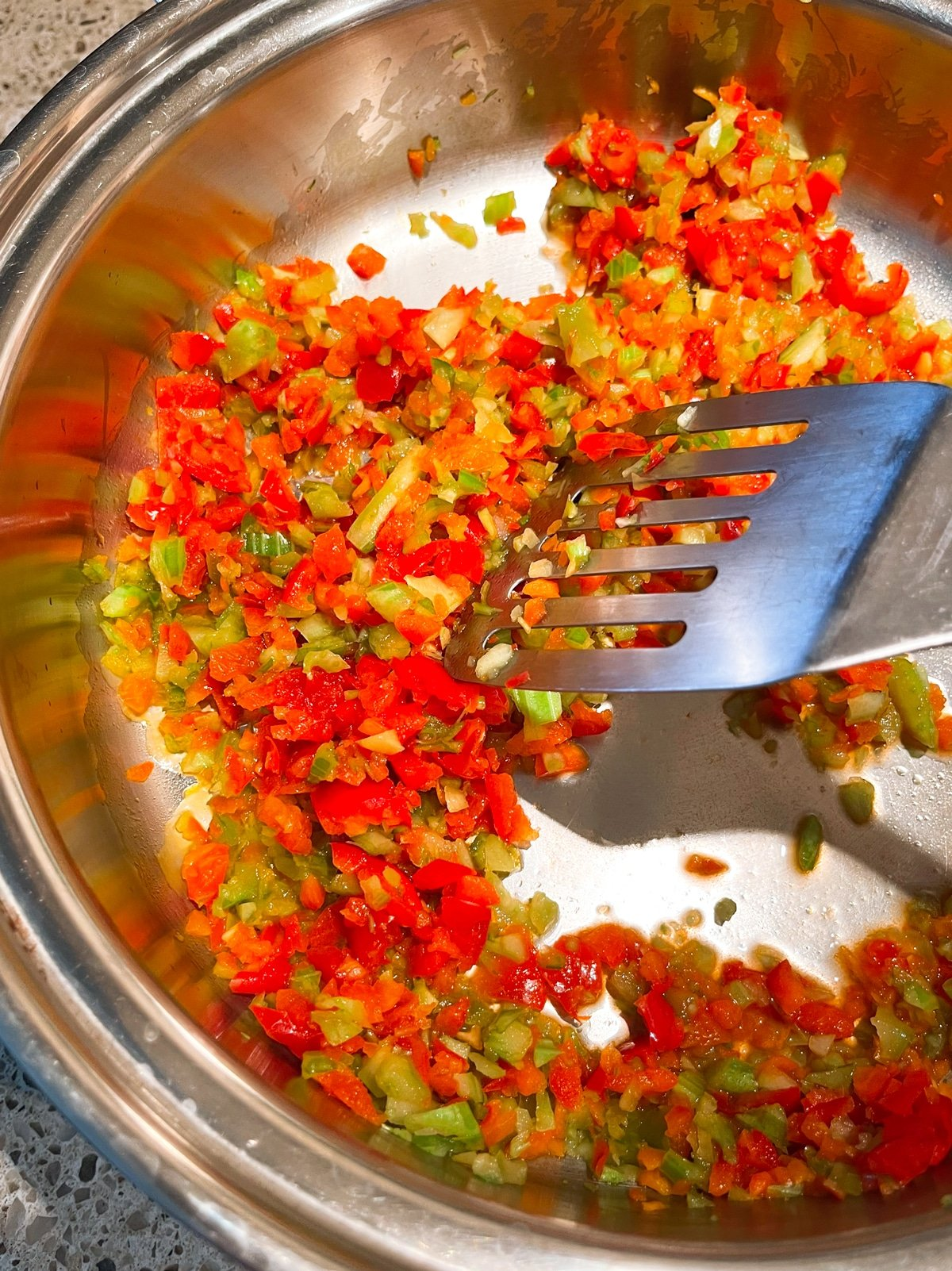 Sauteing chopped vegetables in a skillet.