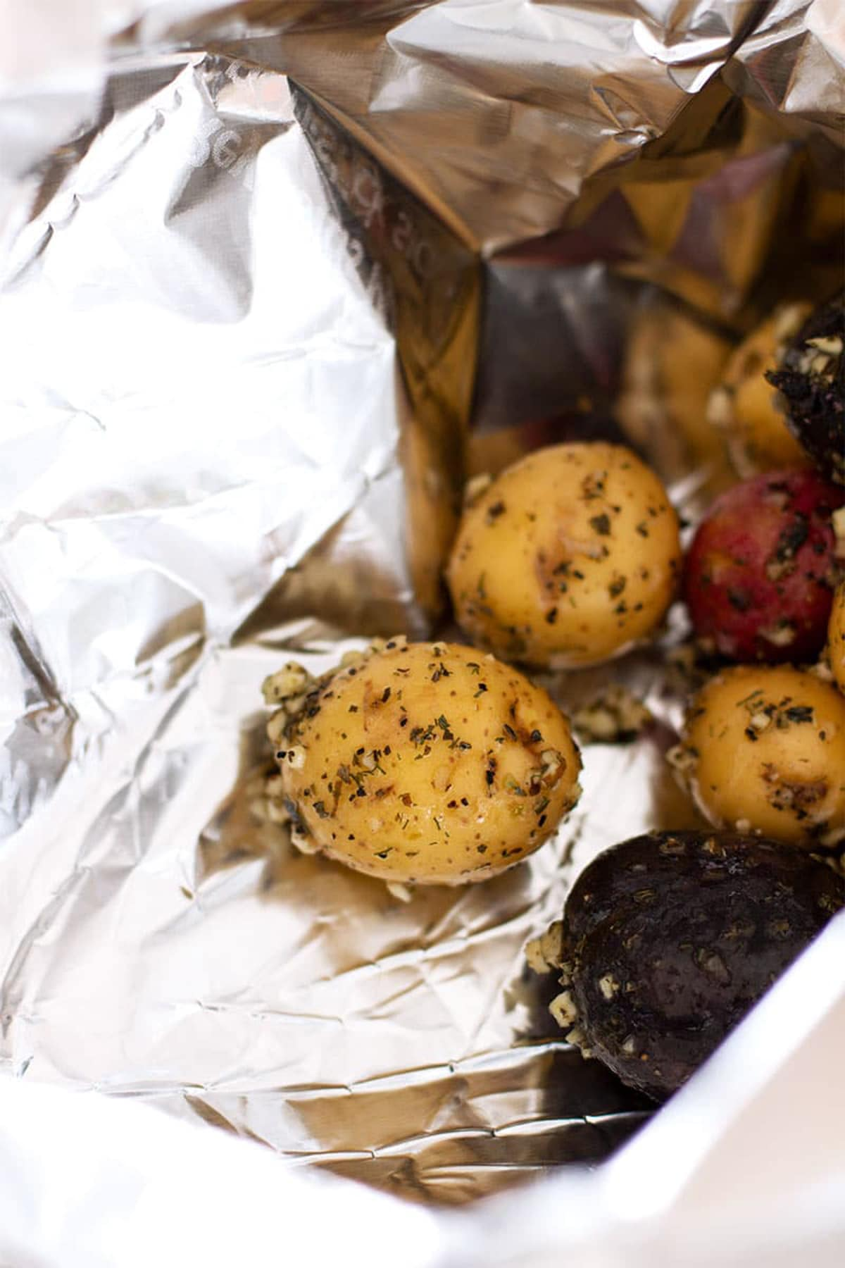 Marinated Garlic and Herb Smoked Potatoes sitting on a piece of aluminum foil.