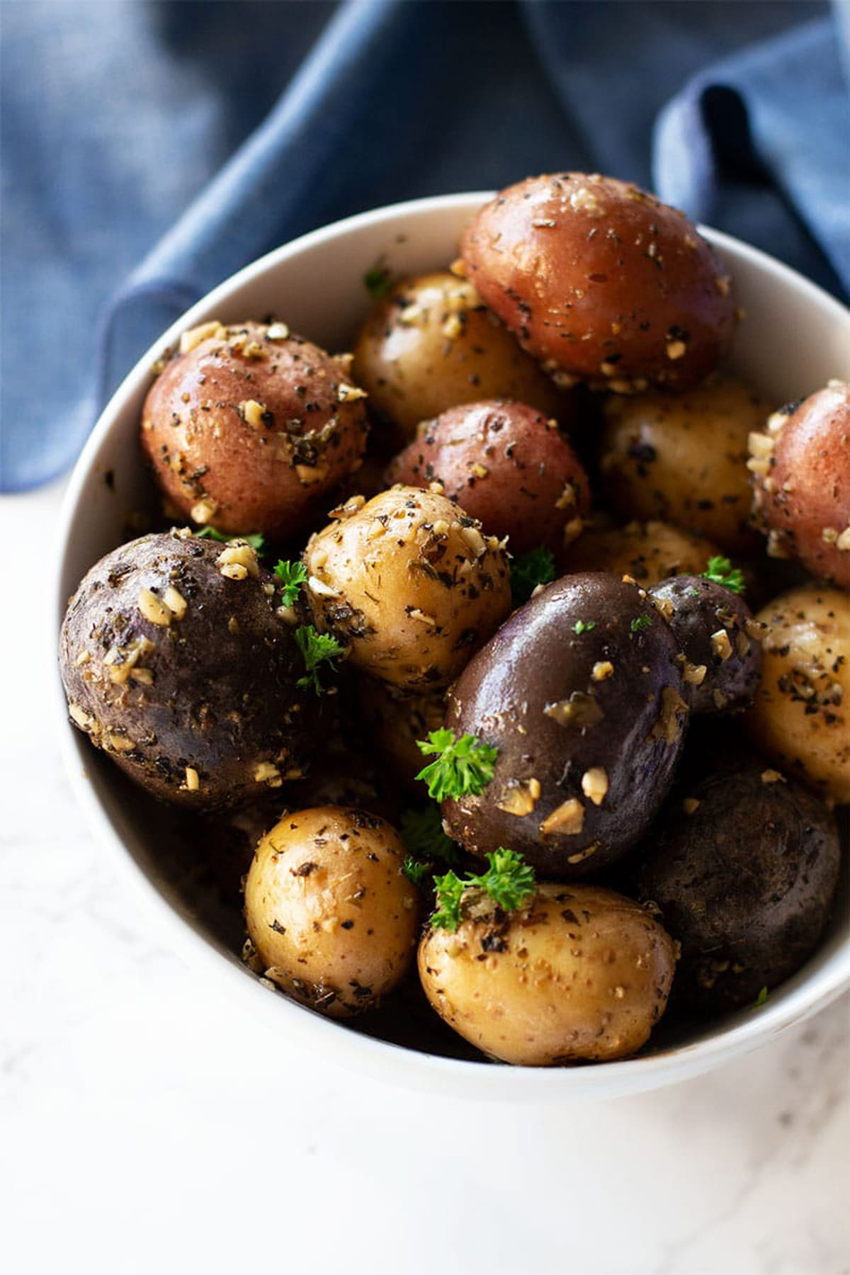 Smoked potatoes in a white bowl covered in garlic and parsley.