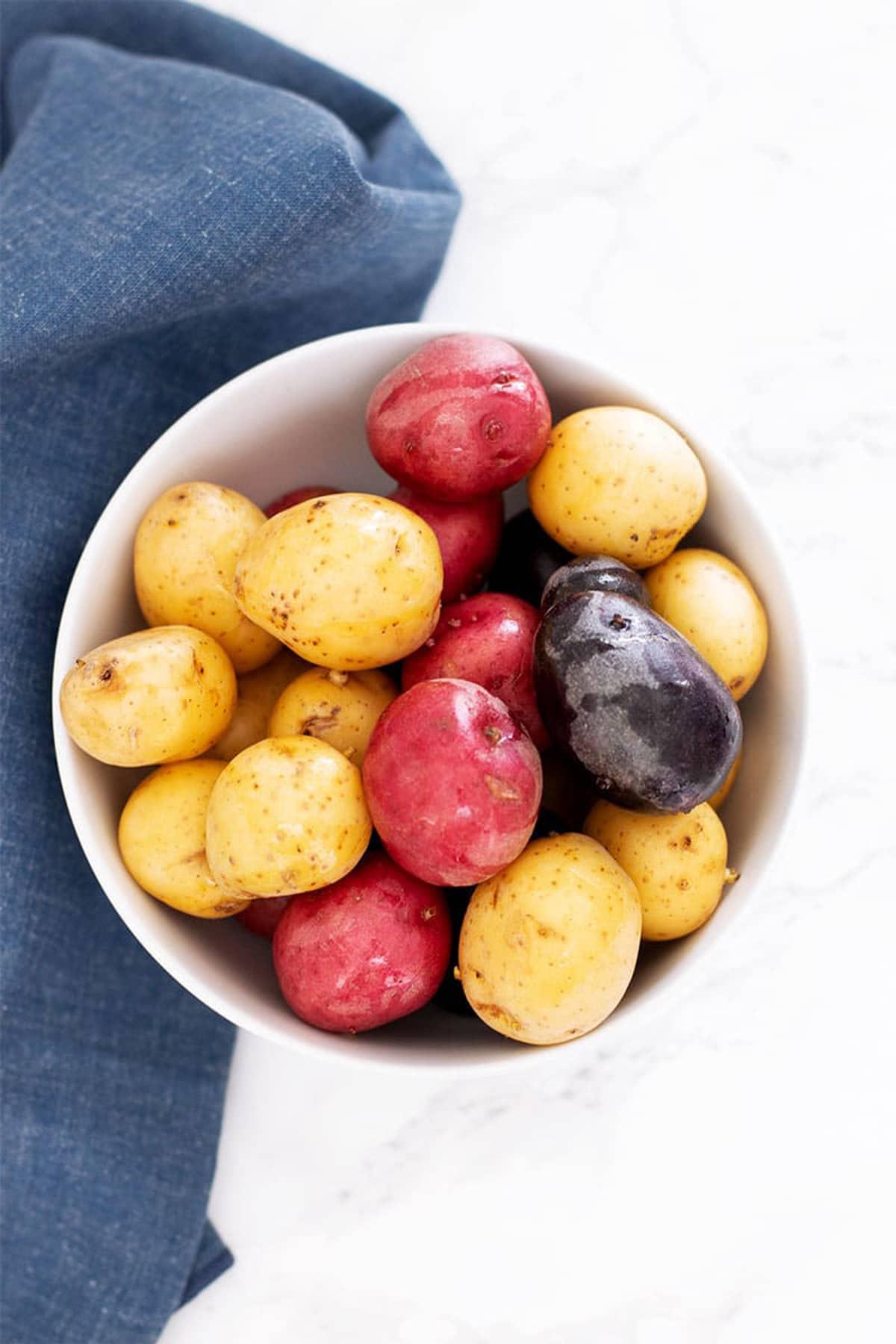 White bowl containing mini gemstone potatoes sitting on a white table, blue napkin around bowl