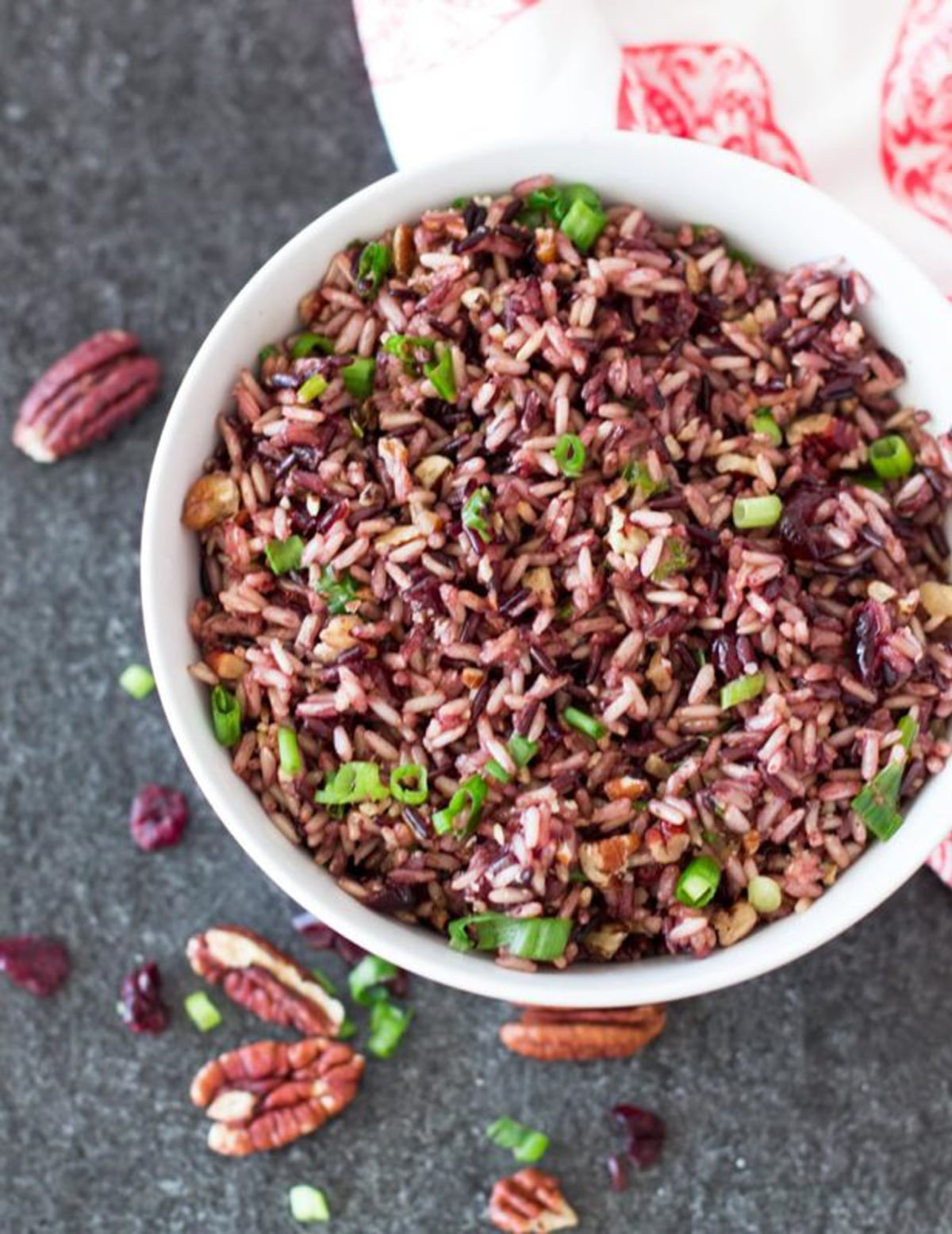 White bowl containing wild rice topped with scallions, pecans and dried cranberries on table.