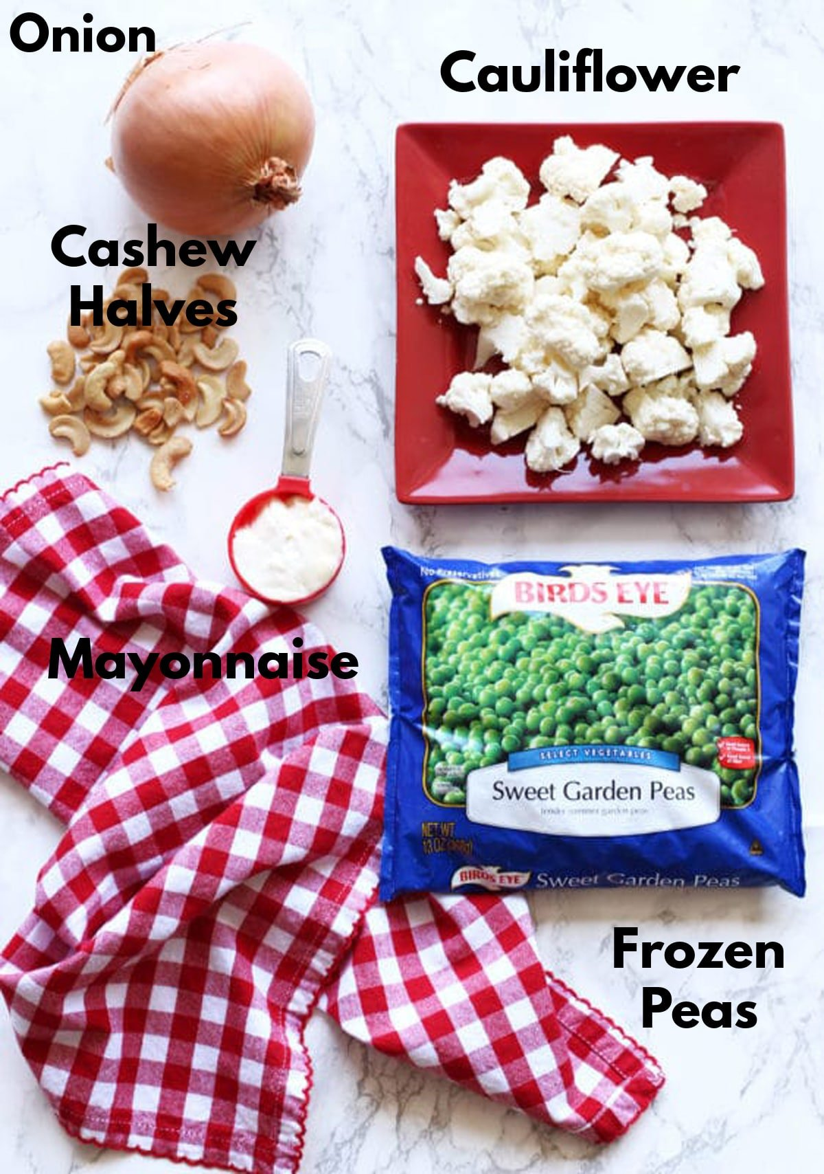 Cauliflower florets, onion, cashew halves, mayonnaise, and frozen peas on a marble countertop.