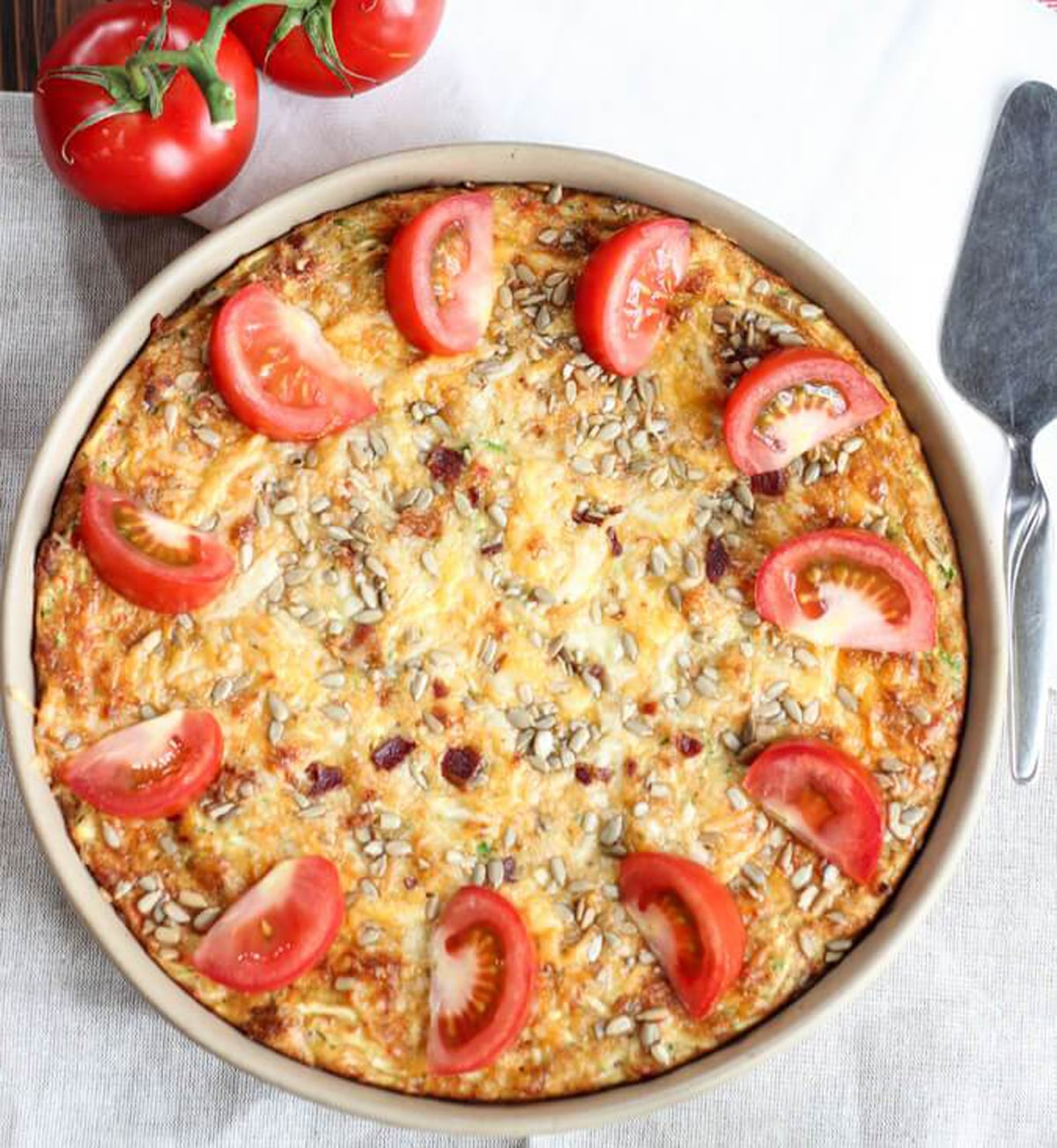 A close up of a round quiche with sliced tomatoes on top.
