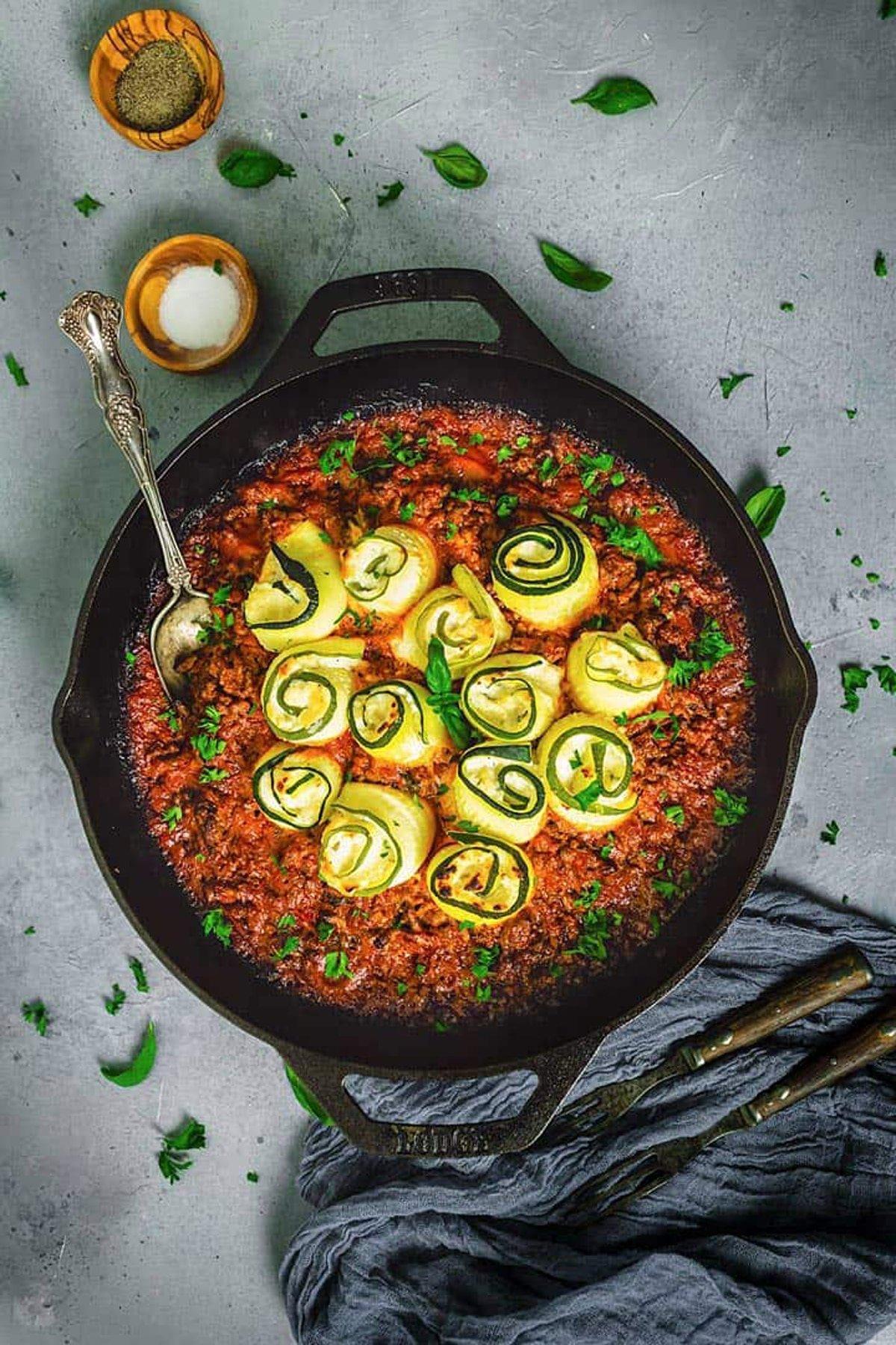 Zucchini rolls in a cast iron skillet of marinara sauce.