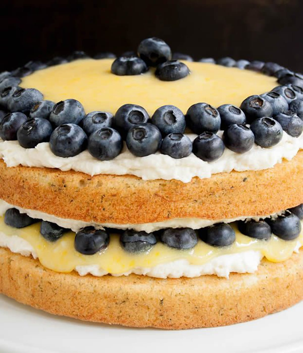 A close up of a two-layer cake with blueberries on the cake