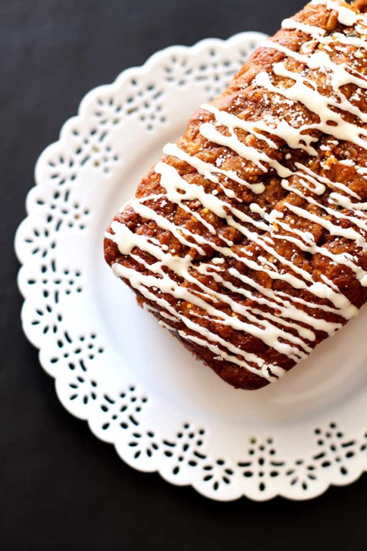 Loaf of zucchini bread glazed with frosting on a plate.