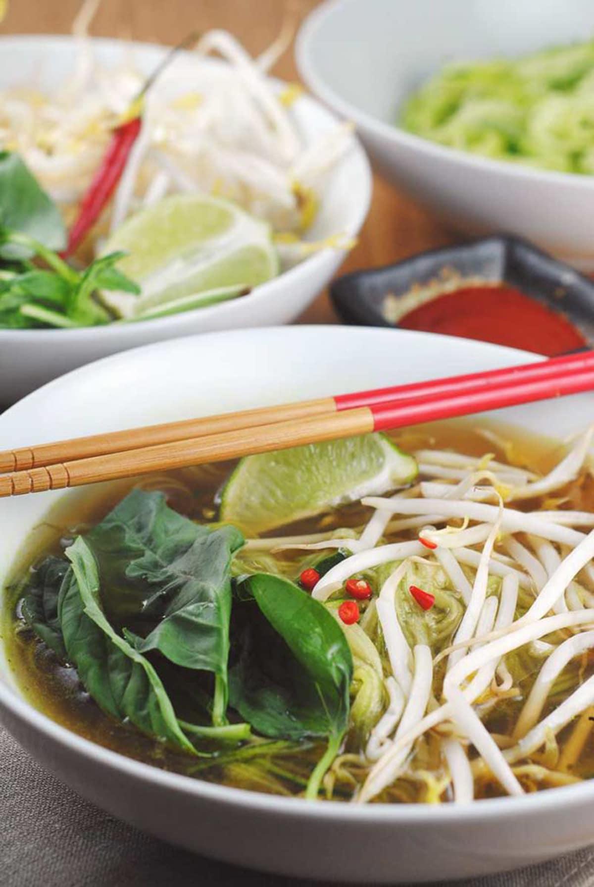 A bowl of zucchini noodle soup with chopsticks.