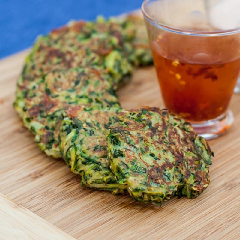 A row of small zucchini pancakes on a wood table.