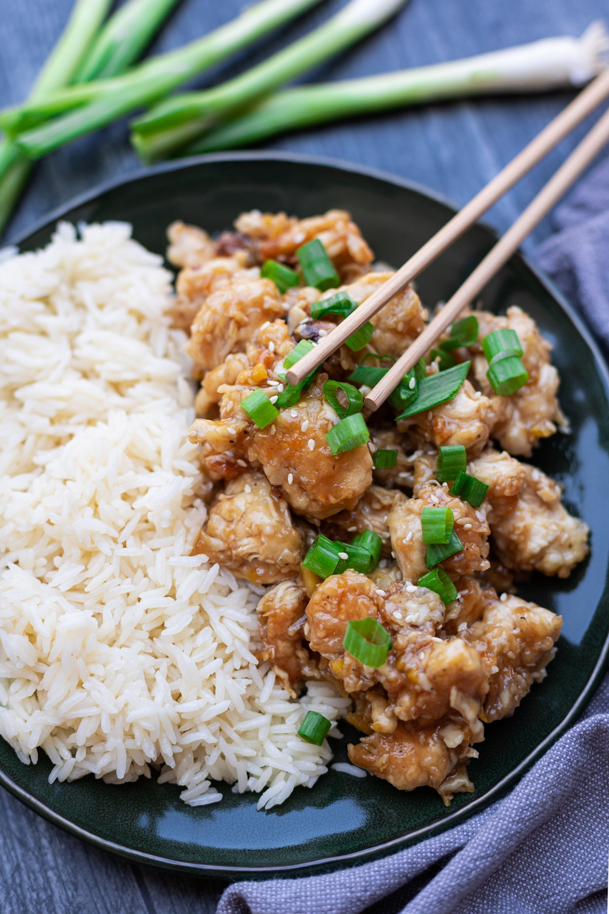 Sesame chicken on a plate with rice, chopsticks on chicken.