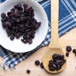 Wooden spoon filled with dried blueberries.