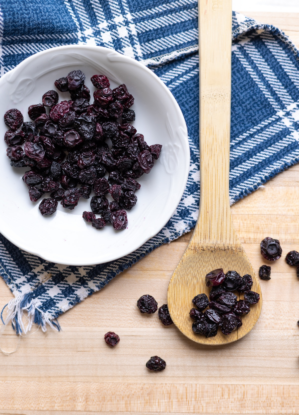 Dehydrated blueberries on a counter, Spoon full of dried berries.