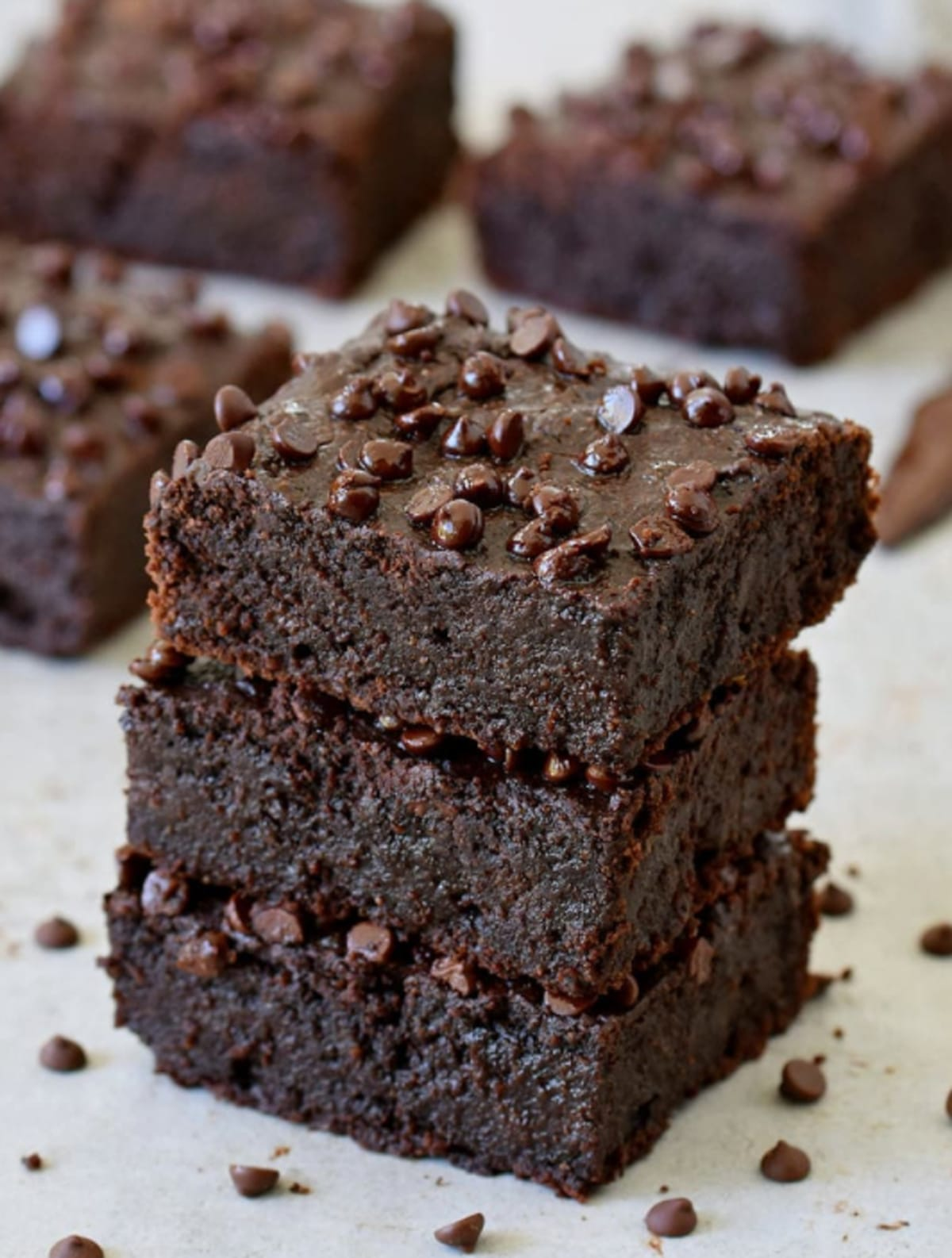 Zucchini brownies on a plate topped with chocolate chips.