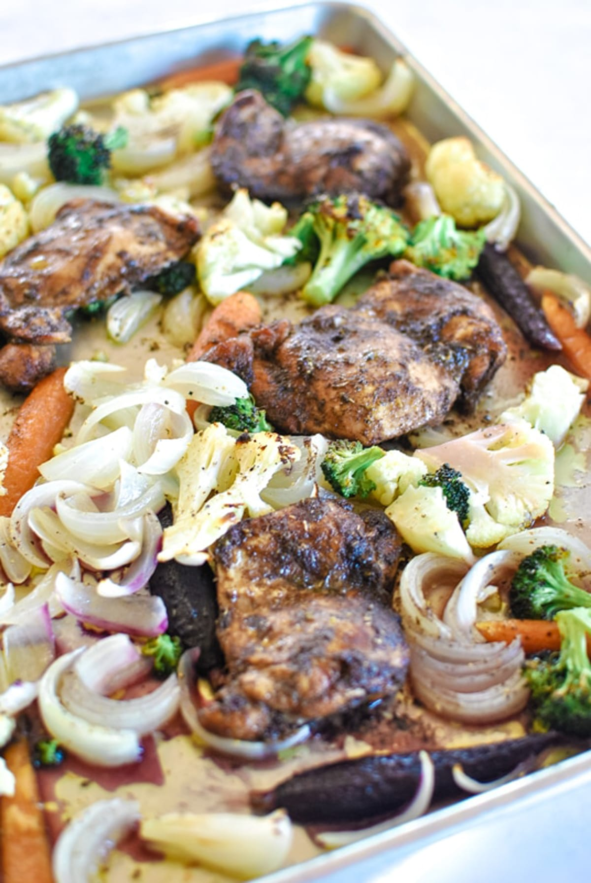 Sheet pan dinner containing baked chicken thighs and vegetables.