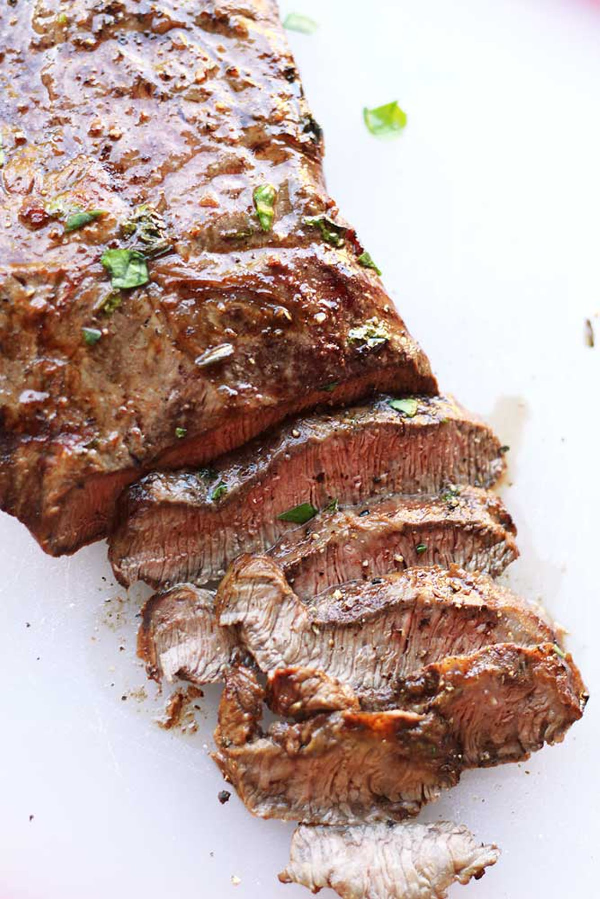 Sliced marinated flank steak sitting on a white table, topped with fresh parsley and fresh ground pepper.