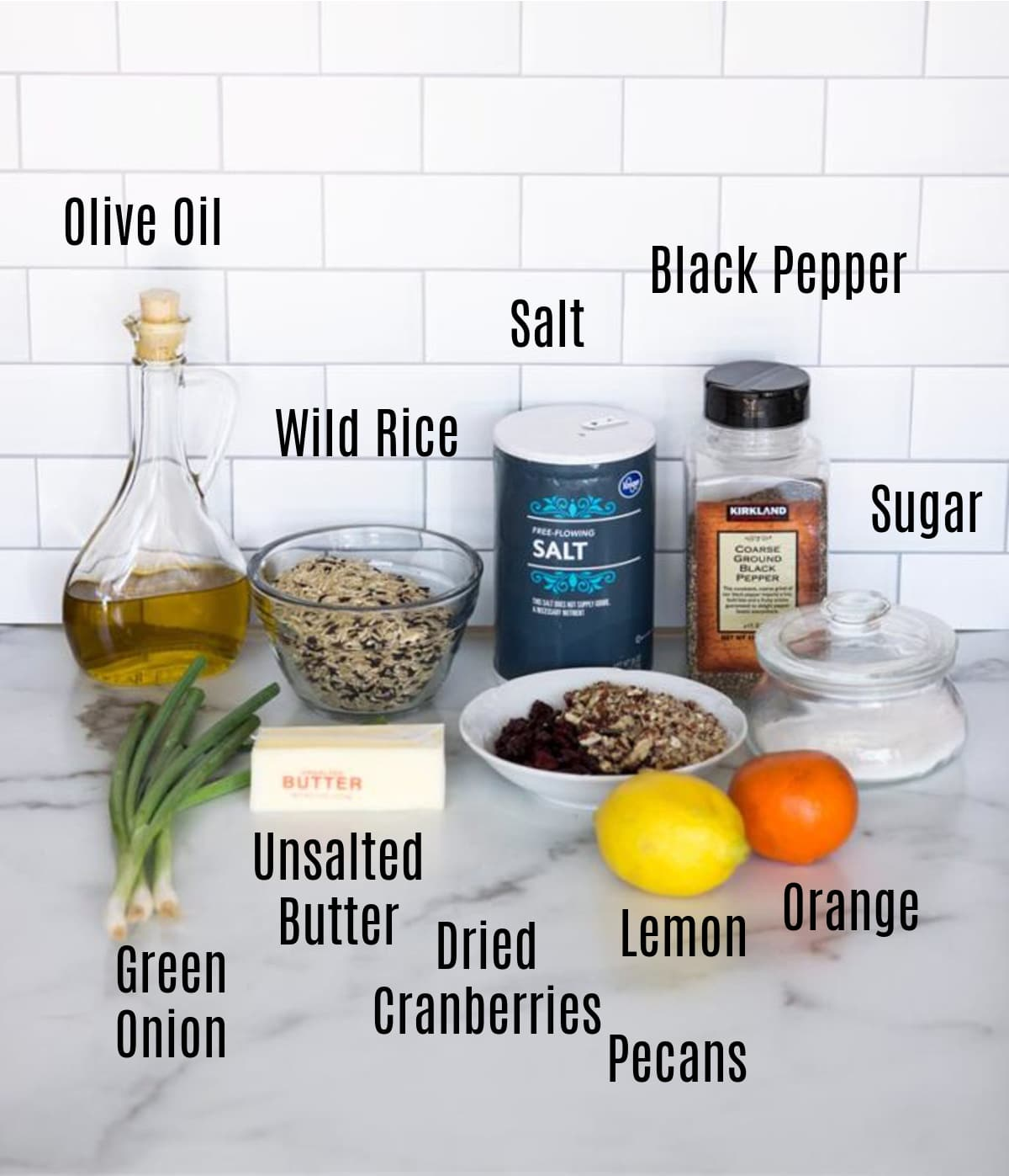 olive oil, rice, citrus vinaigrette dressing ingredients, pecans, and scallions on a counter.