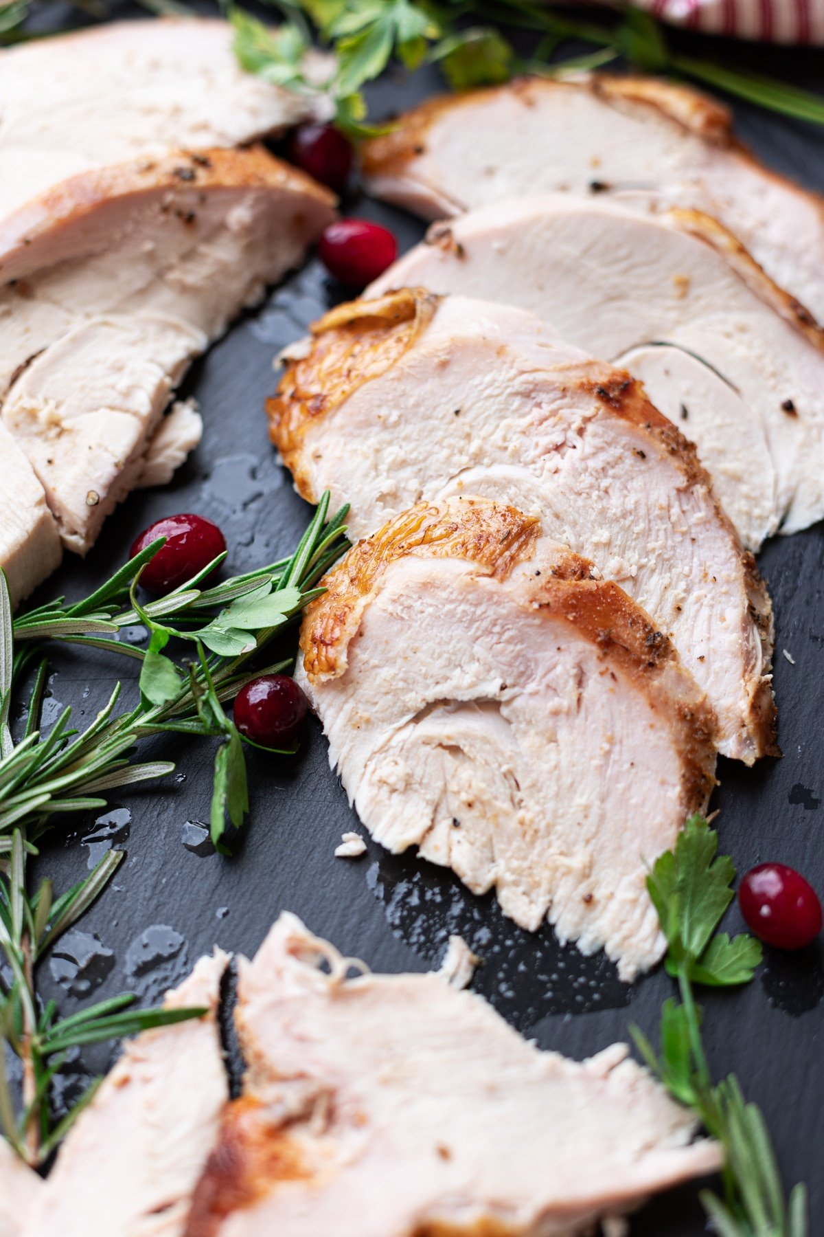 Sliced turkey breast on a plate, cranberries and rosemary on table.
