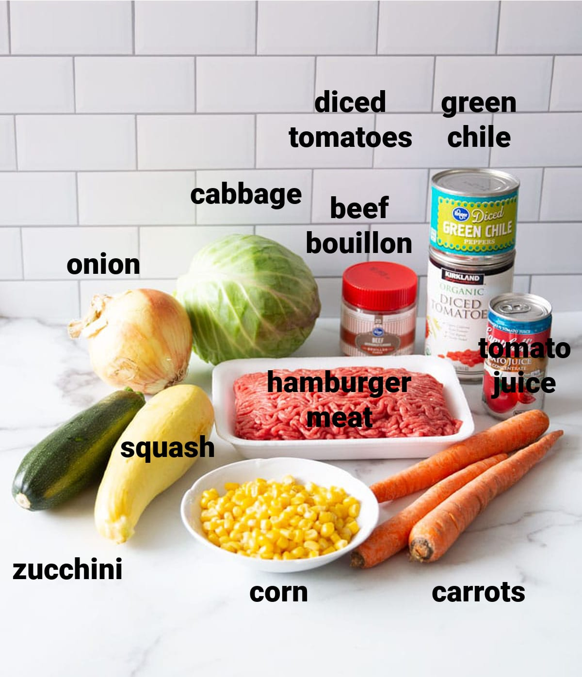 Ground Beef, green chile, bouillon cubes, cabbage, zucchini, squash, corn, carrots on counter.