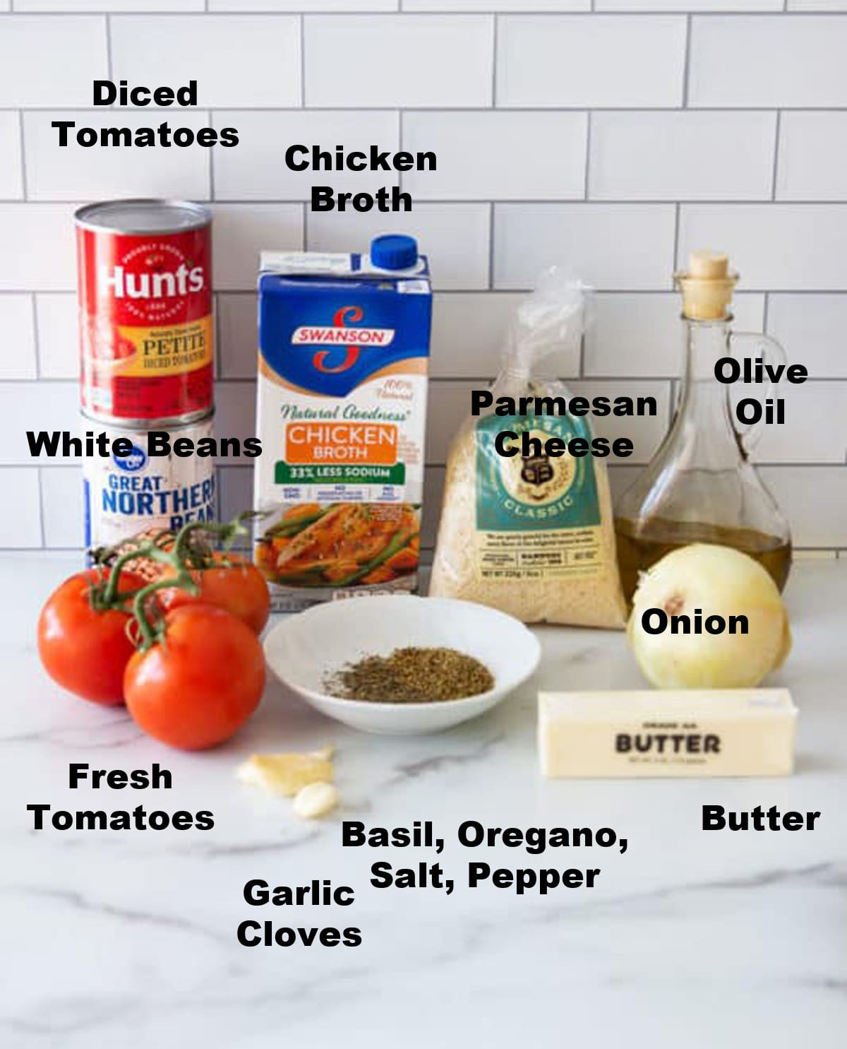 Tomatoes, can of white beans, can of diced potato, chicken broth, Parmesan cheese, herbs, onions, butter, and olive oil on white counter.