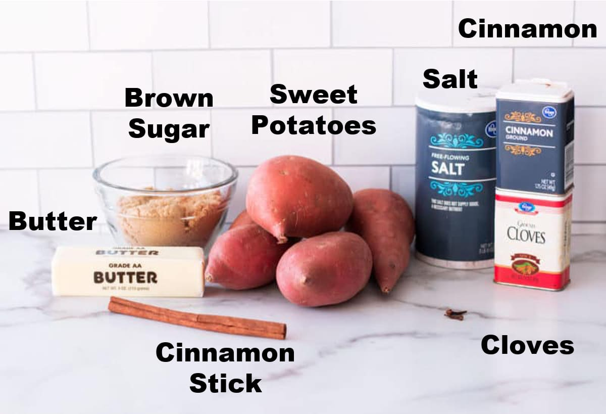 butter, brown sugar, cinnamon stick, sweet potatoes, salt, cinnamon, ground and whole cloves on counter.