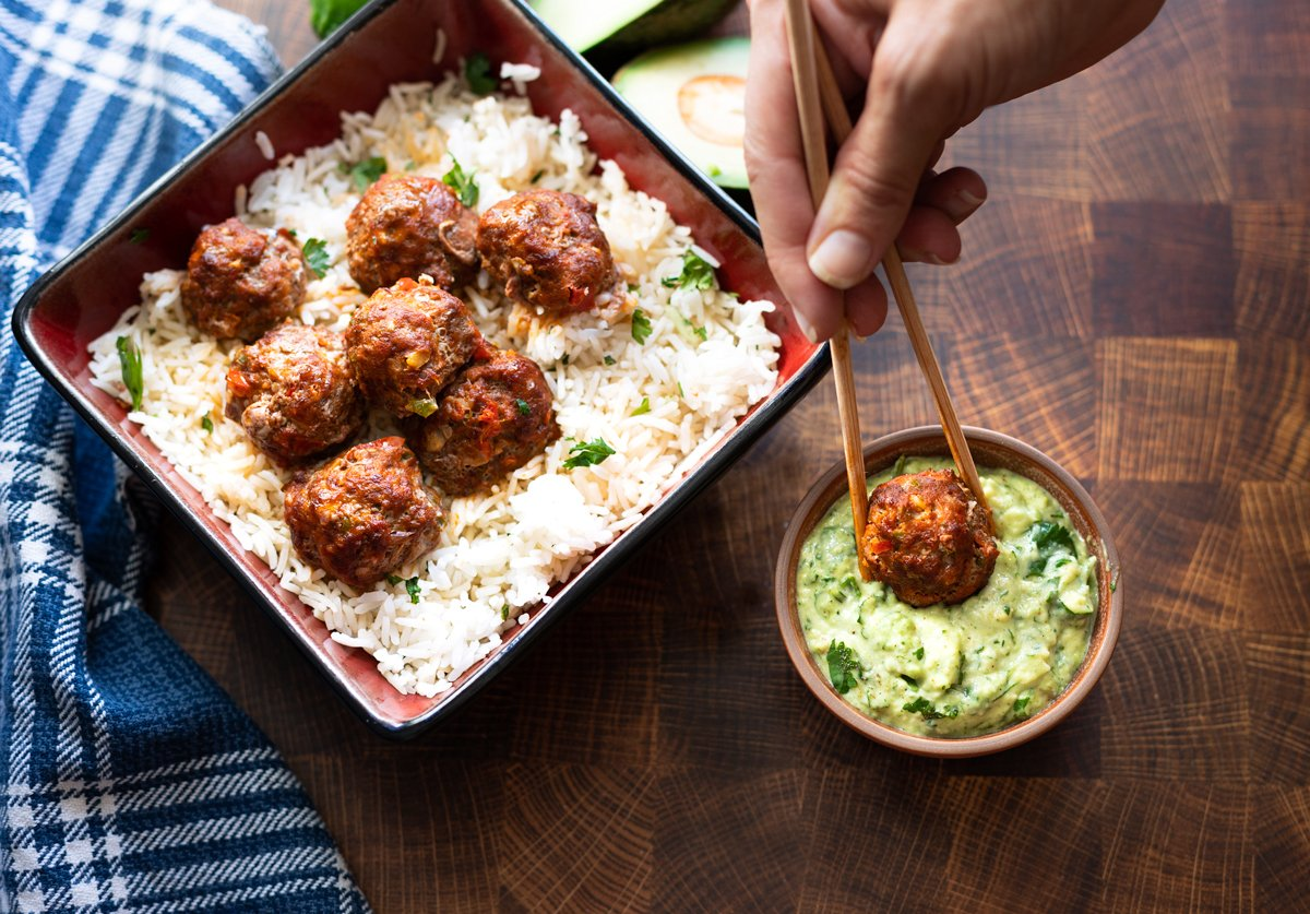 person dipping a turkey meatball in avocado sauce.
