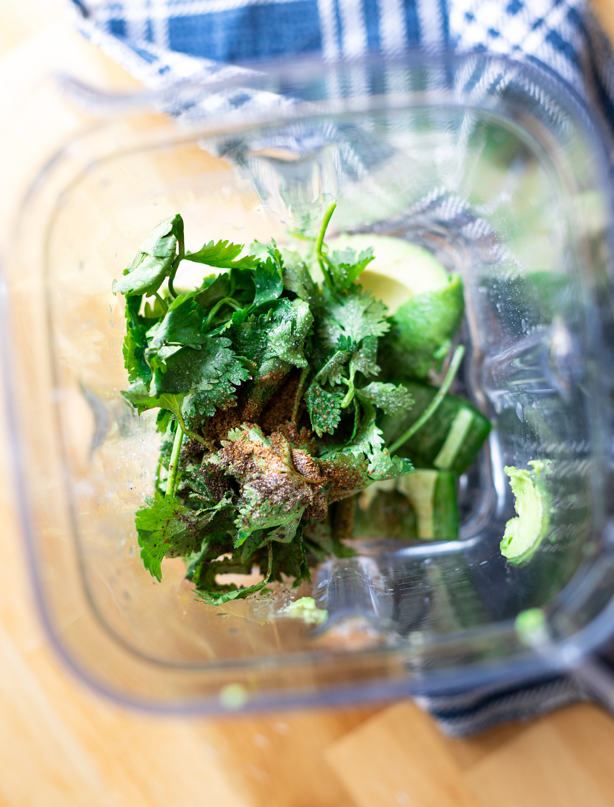 food processor with cilantro, avocado, and seasonings.