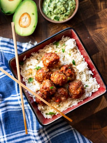 Dish containing turkey meatballs served over white rice.