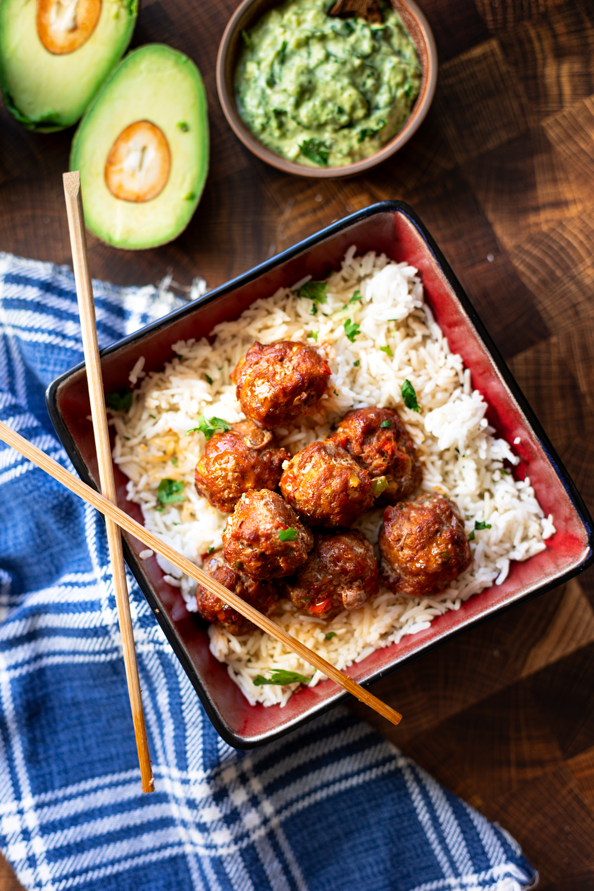 Meatballs in a bowl in a bed of rice, chopsticks on bowl.