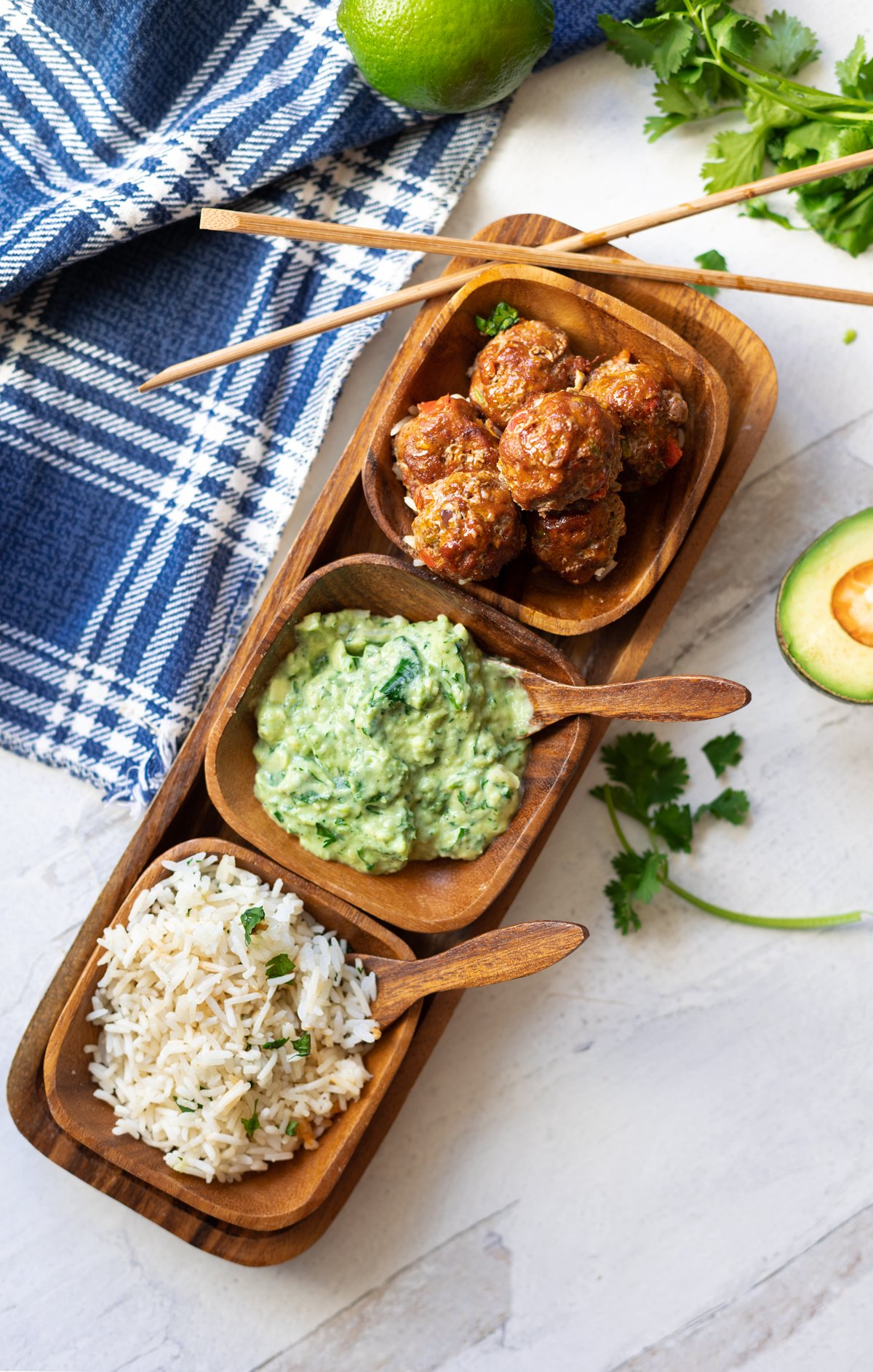 Rice, avocado sauce, and meatballs in a serving dish with chopsticks.
