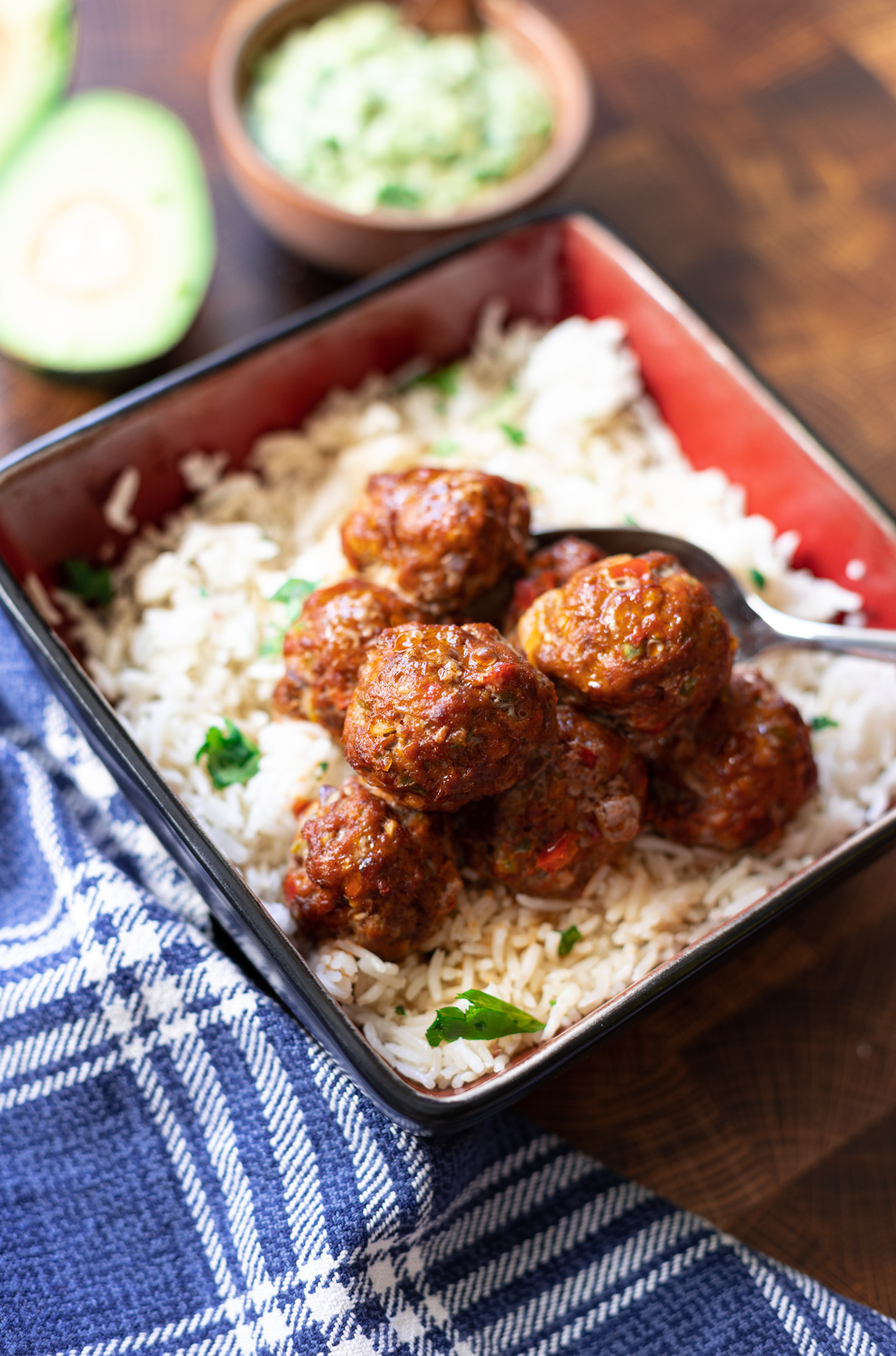 bowl containing rice topped with meatballs, avocado sauce in a dish on table.